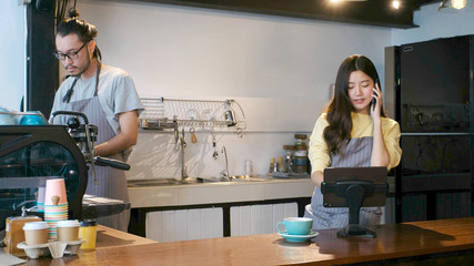 Young asian barista taking order by mobile phone and digital tablet at counter in cafe coffee shop, asia small business owner, start up
