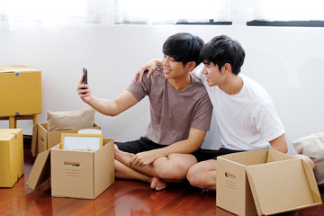 Asian homosexual male lgbt couple, Young asian gay man holding mobile phone take selfie while moving into new home, Asia homosexual boys using smartphone make vdo call while unpacking,  lgbt concept