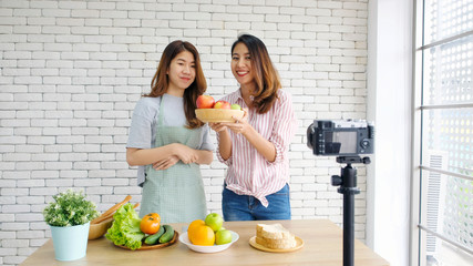 Two young asian women food bloggers talking while recording video with happy moment, vlog concept, people and technology communication