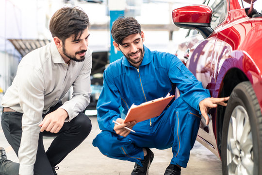 Vehicle maintenance handsome man servicer explain car condition to male customer in garage. Automotive mechanic pointing at tyre rubber condition needed for the replacement. Car repair service concept