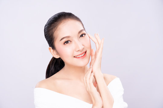 Beautiful Young Asian woman with clean fresh white skin touching her own face softly in beauty pose. Girl touching with fingers in white background. Facial treatment, cosmetology, spa, make up concept