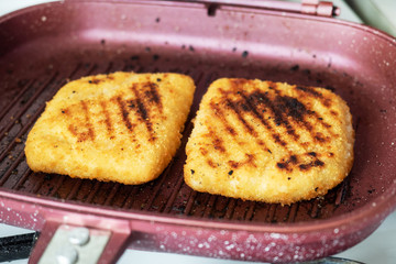 Schnitzel fried on the grill pan. Two pieces of Cordon Bleu with ham and cheese in a pan.