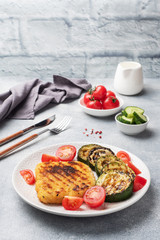Schnitzel of chicken and zucchini cooked on the grill. Fresh tomatoes on a plate. Ready delicious dinner lunch. Copy space.