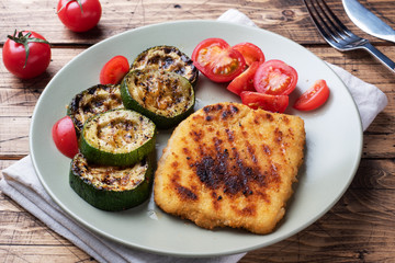Schnitzel of chicken and zucchini cooked on the grill. Fresh tomatoes on a plate. Ready delicious dinner lunch. Wooden background