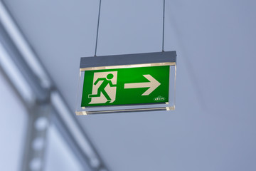 Vienna, Austria - Jan 29, 2020: View on illuminated emergency exit sign. With running figure and arrow to the right. Neutral, white background. Modern design. Hanging from the ceiling.