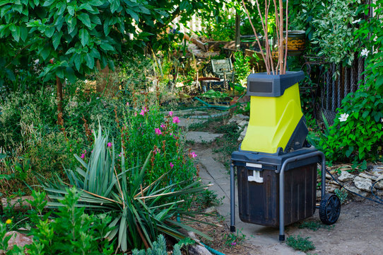 Small portable electric woodchipper in a garden