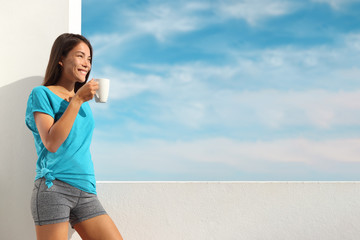 Woman drinking tea coffee mug happy summer lifestyle. Asian girl enjoying breakfast hot drink beverage for healthy eating. Smiling young relaxing at home window after yoga class.