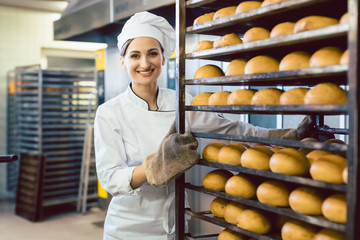 Keuken foto achterwand Bakkerij Baker rolling trays with fresh bread thru the bakery