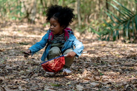 American mixed race kid Girl playing with Net in Jungle.