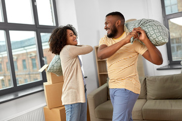 moving, people, repair and real estate concept - happy african american couple having pillow fight at new home