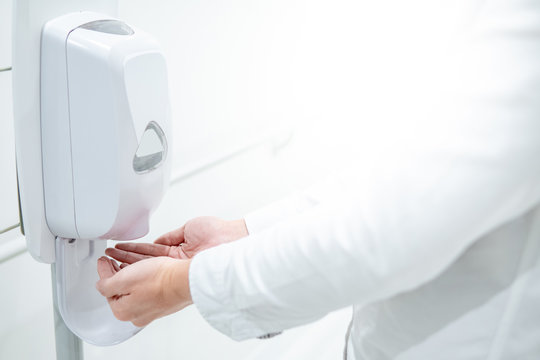 Male patient hands using automatic alcohol dispenser for cleaning hand in hospital. Infection prevention concept. Save and clean in public medical center area.