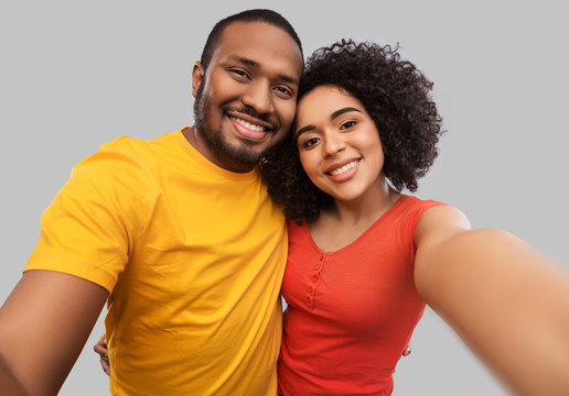 relationships and people concept - happy african american couple taking selfie over grey background