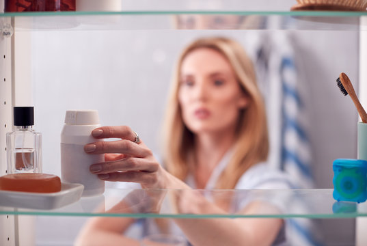 View Through Bathroom Cabinet Of Young Woman Taking Medication From Container