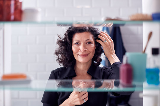 View Through Bathroom Cabinet Of Mature Businesswoman Getting Ready For Work Checking Hair