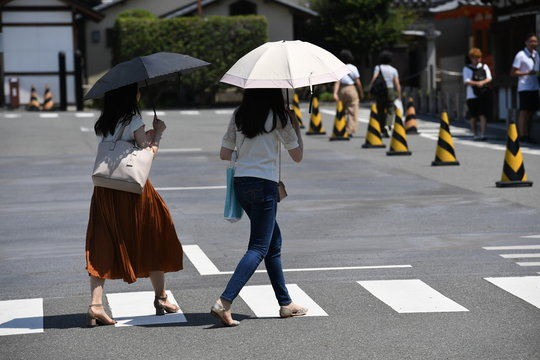 Two young japanese woman with umbrellas walking over a zebra crossing in Kyoto-Japan.