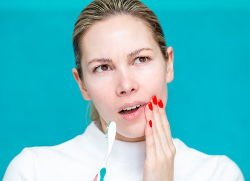 girl holds on to a bad tooth, toothache, severe sharp pain, oral cavity
