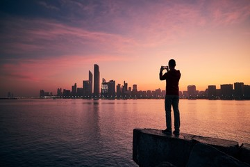 Man with mobile phone at sunrise