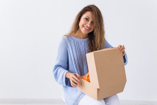 Online shopping, delivery and fashion concept - Woman sitting on sofa at home opening online clothing purchase