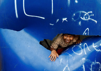 A boy reacts as he looks on from the plastic water tank in Jakarta