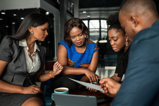 African businesspeople discussing paperwork together during an office meeting
