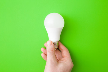 Young man hand holding led light bulb on bright green table background. Closeup. Energy saving. Point of view shoot. Top down view.