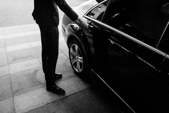 Valet's Hand Opening Grey Car Door On Street
