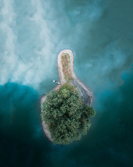 Magical island on a azure blue lake with boat on the shore