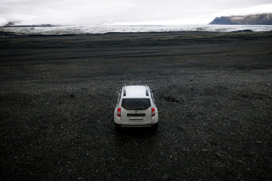 Offroad Car on black gravel in Iceland with glacier in the background
