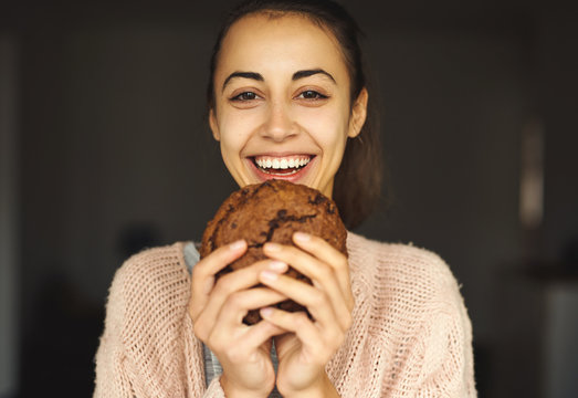 funny portrait of happy smiling woman posing with big chocolate cookie and looking at the camera. food, sweets and bakery concept.