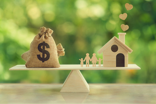 Property investment and house mortgage concept : Wooden home, Family member  and US dollar hessian bags on wooden balance scale. depicts family financial management for a residence.