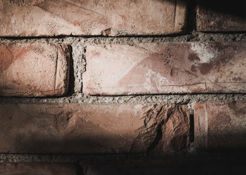 Close up of a brick wall with harsh light from the upper left and shadows on the wall