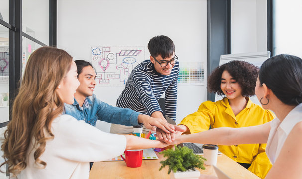 Young Asian people stacking hands for teamwork concept