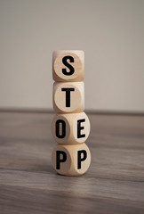 Tower made of cubes and dice with step and stop on wooden background