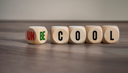 Cubes and dice with words cool and uncool on wooden background