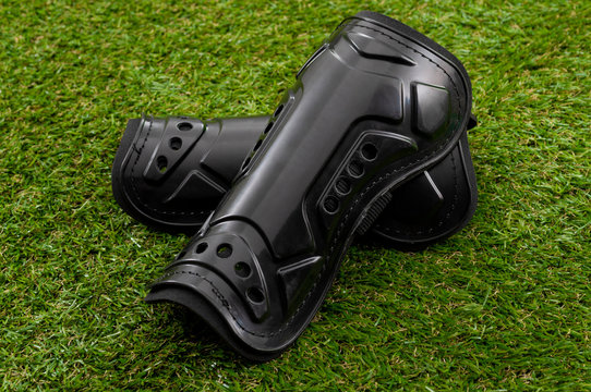 Football equipment, injury and bruise prevention and soccer gear concept with tough black shin guards isolated on grass background