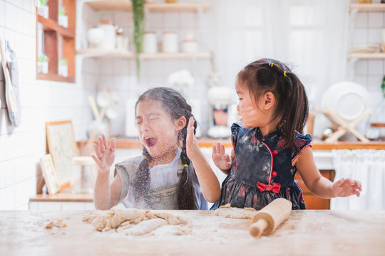Two cute girls making cake / cooking in kitchen at home