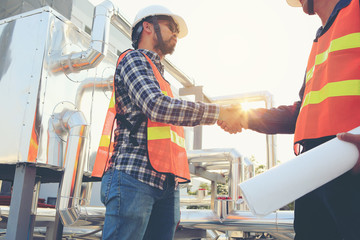 Two construction engineers shake hands in construction site
