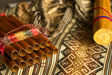 Close up view of Peruvian pan flute and rain stick on traditional colorful textile. Concept of traditional Andean music. Fototapete