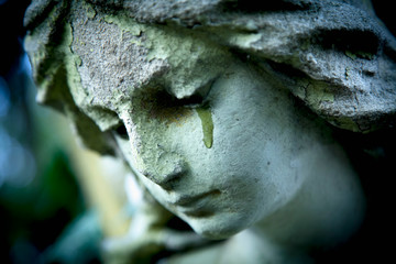 Fototapete -  Close up ancient statue of crying angel with tears in face as symbol of death and end of human life.