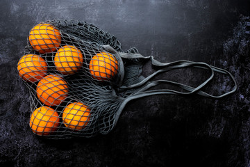 High angle close up of oranges in grey net bag on black background.