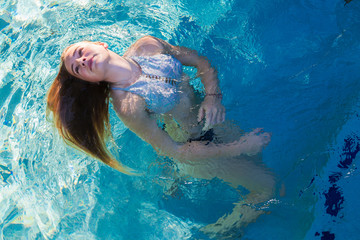 A teenage girl swimming in a pool, floating head back hair spread on the water. ,St Simon's Island