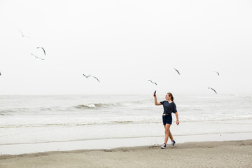 teen girl talking pictures with smart phone at the beach, St. Simon's Island, Georgia,St Simon's Island