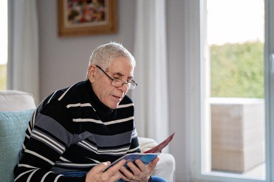 Old adult grey haired man in glasses reading magazine sitting on sofa alone.  Senior lifestyle.