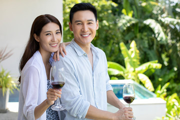 Happy young Chinese couple drinking wine on balcony