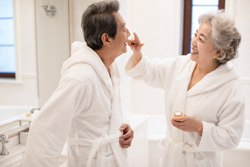 Happy senior Chinese couple applying moisturizer in bathroom