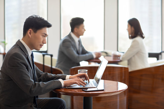 Confident Chinese businessman using laptop in airport lounge