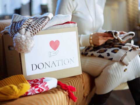 Closeup on donation box and woman packing clothes in background