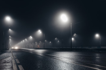 Foggy misty night road illuminated by street lights