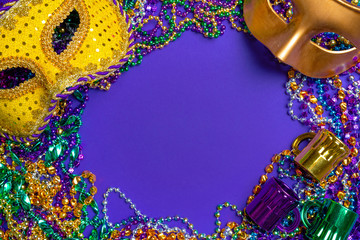 Wall Mural - Colorful Mardi Gras mask on purple background with beads