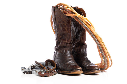 Western boots and a lap or lariat rope and spurs on a white background